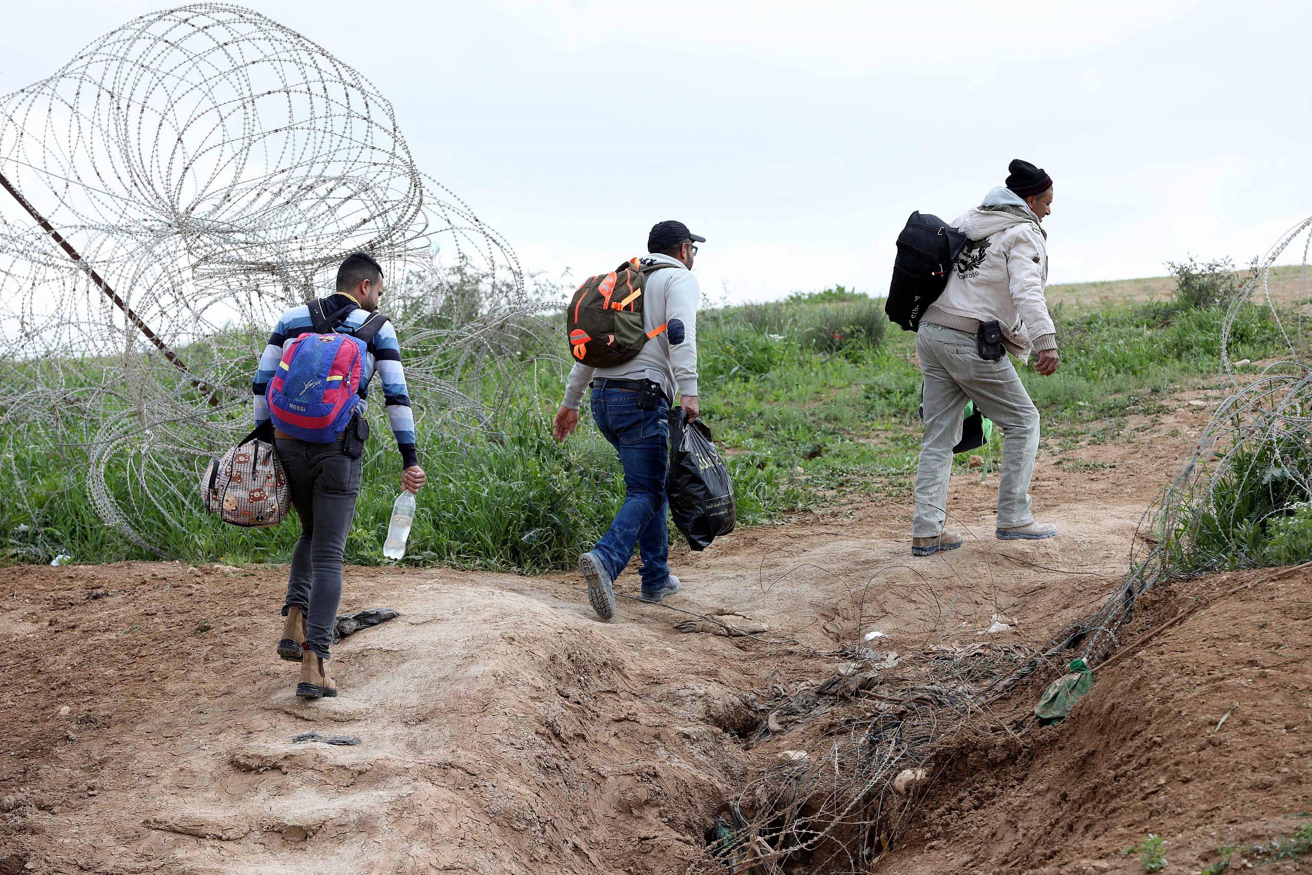 I lavoratori palestinesi della città di Hebron in Cisgiordania trasportano oggetti personali mentre attraversano la barriera di separazione israeliana attraverso un buco, dopo che l'ingresso in Israele è stato bandito in seguito alla diffusione del coronavirus, vicino alla città di Hebron in Cisgiordania, il 22 marzo 2020 ( Wisam Hashlamoun / Flash90)