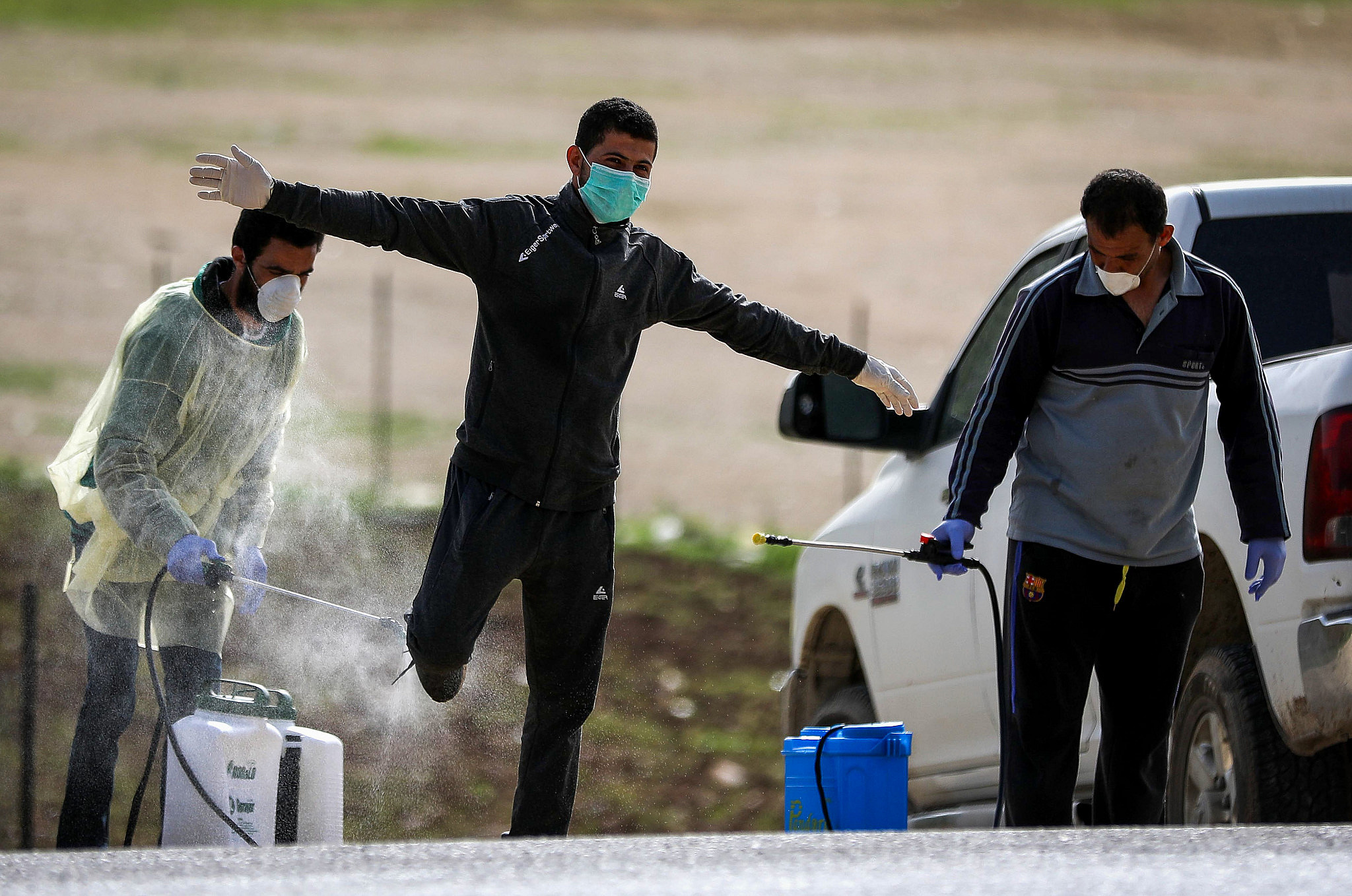 Palestinian health workers disinfectant Palestinian laborers as they cross back from Israel to the West Bank at a checkpoint in Tarqumiya on March 27, 2020. (Wisam Hashlamoun/Flash90)