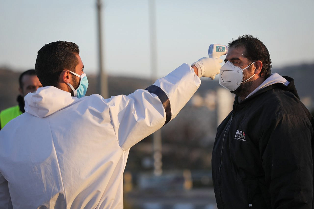 Palestinian medical employees disinfect Palestinian workers who came back from working in Israel at the entrance to the West Bank village of Hussan, to stop the spread of the coronavirus. March 29, 2020. (Nati Shohat/Flash90)