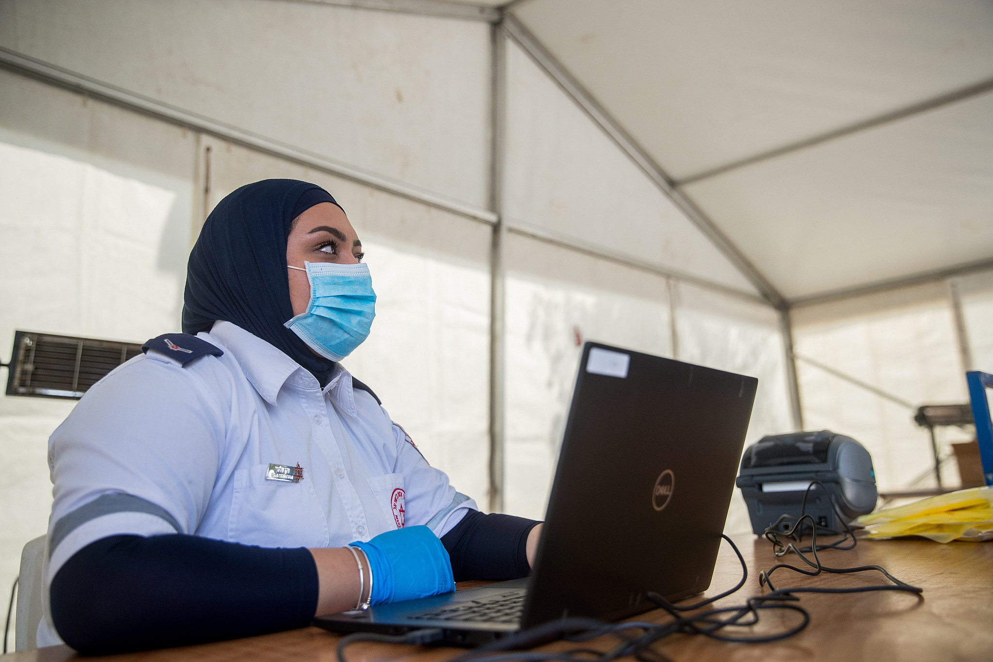 Magen David Adom medical workers seen at a drive-through site to collect samples for coronavirus testing, at the entrance to the East Jerusalem neighborhood of Jabal Mukaber, on April 2, 2020. (Yonatan Sindel/Flash90)