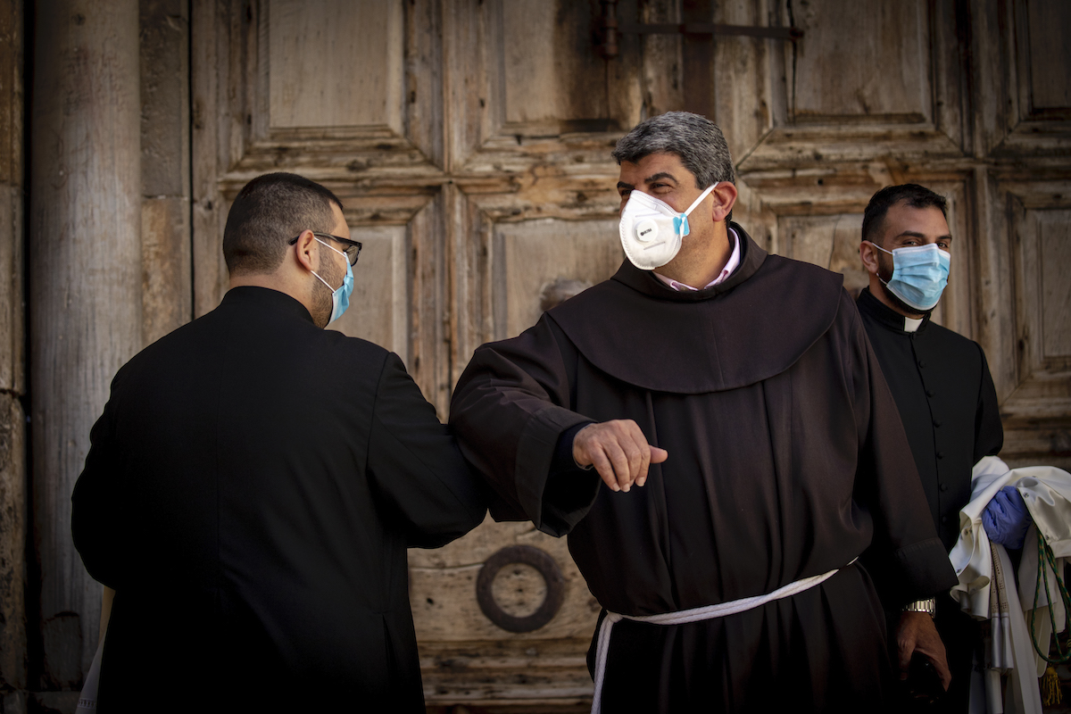 Monks wearing face masks and gloves salute each other outside the Church of the Holy Sepulchre which was closed due to the coronavirus, in Jerusalem's Old City, on April 4, 2020. (Olivier Fitoussi/Flash90)