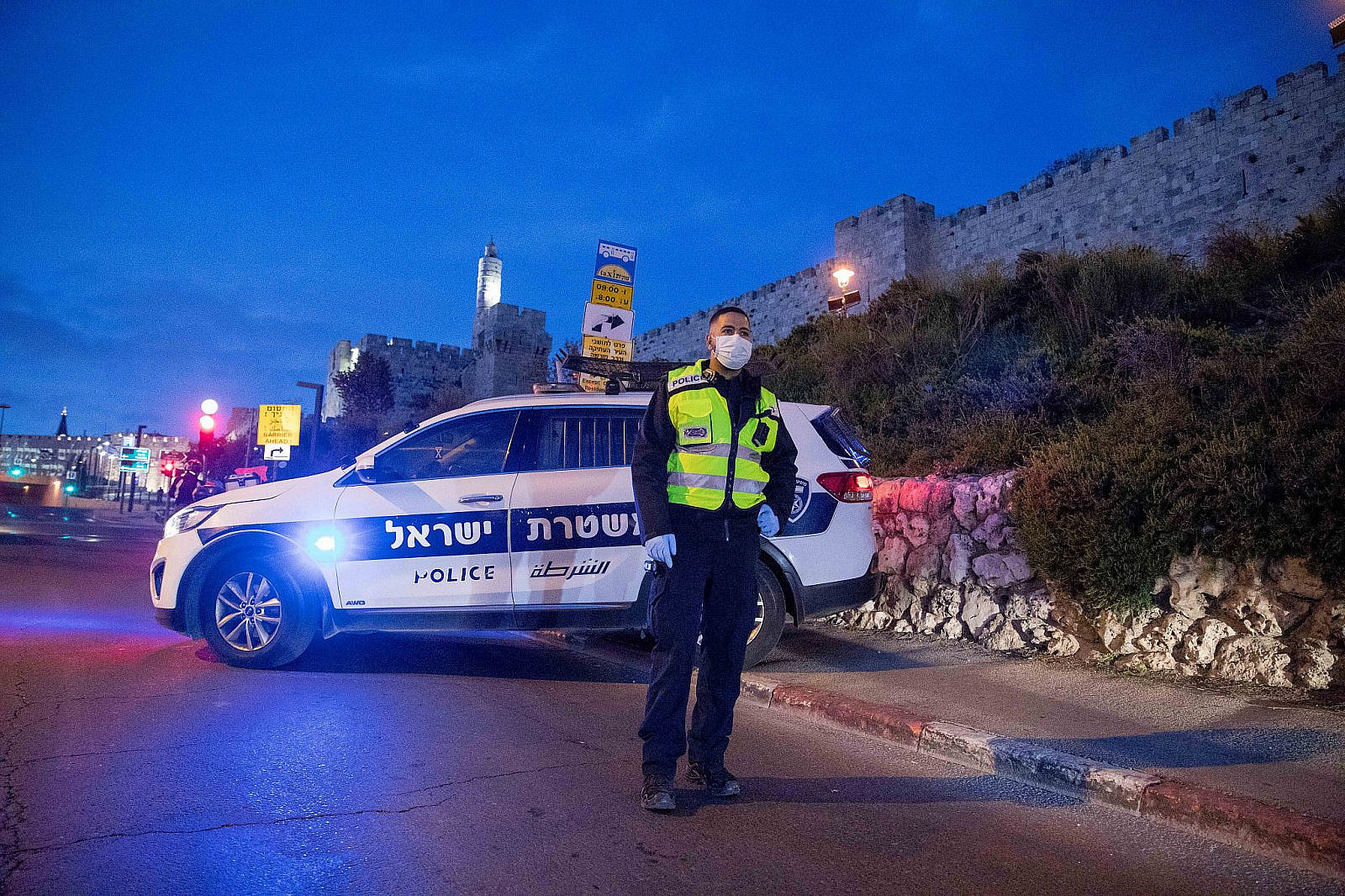 """An Israeli police officer stands at a temporary """"checkpoint"""" near the Old City in Jerusalem. April 7, 2020. (Nati Shohat/Flash90)"""