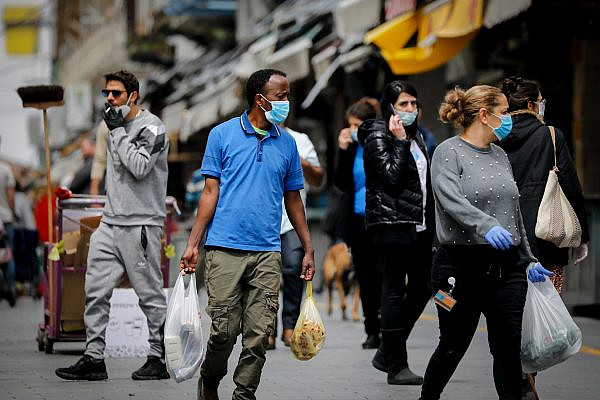 People wear protective face masks as they shop for food at the Mahane Yehuda market in Jerusalem on April 7, 2020. (Olivier Fitoussi/Flash90)