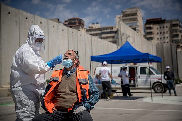 Magen David Adom medical workers seen at a drive-through site to collect samples for coronavirus testing near the separation wall on April 16, 2020, Shuafat Refugee Camp, East Jerusalem. (Photo by Yonatan Sindel/Flash90)