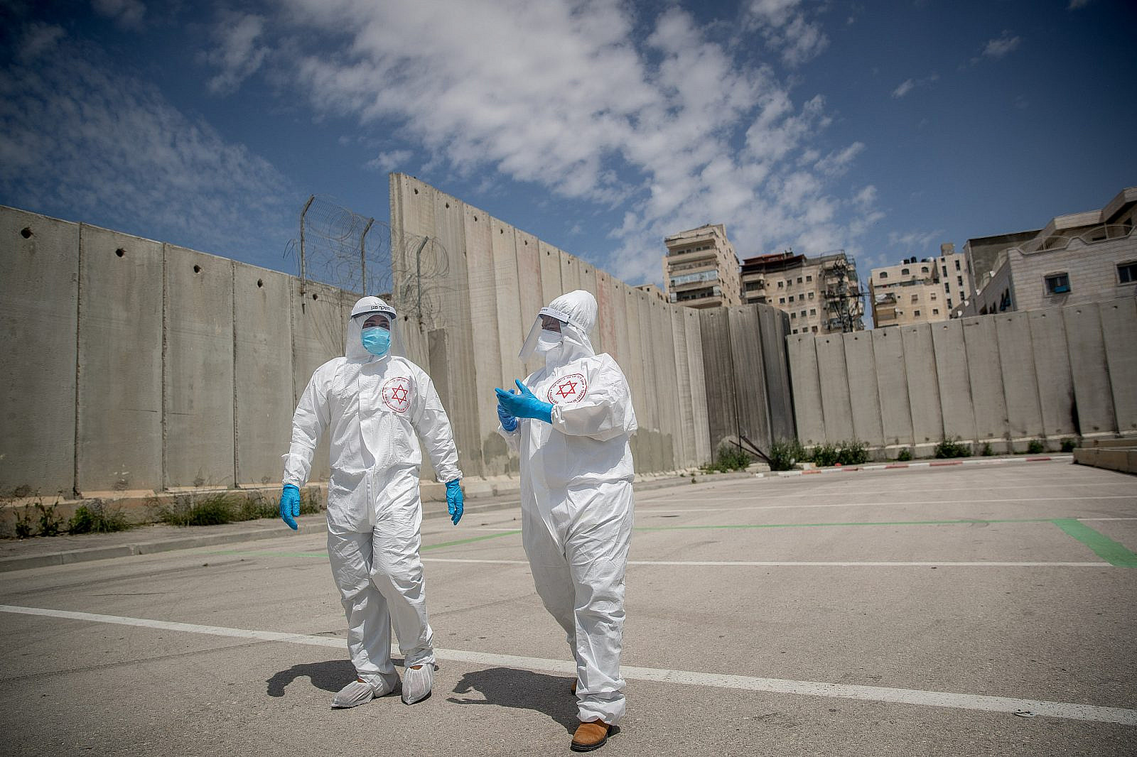 Magen David Adom medical workers seen at a drive-through site to collect samples for coronavirus testing, near the separation wall at the Shuafat Refugee Camp, Jerusalem, April 16, 2020. (Yonatan Sindel/Flash90)