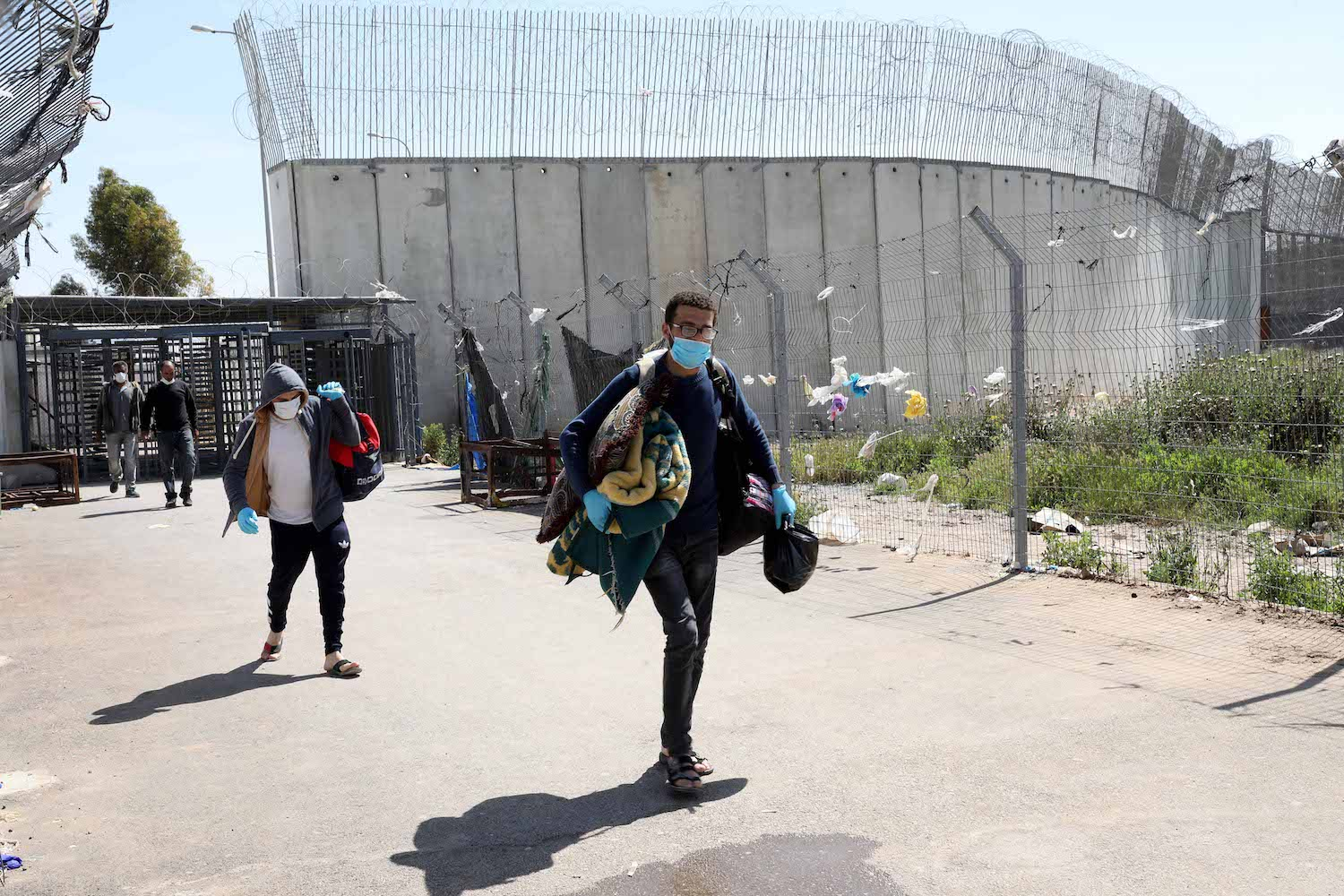Palestinian workers cross back from Israel at a checkpoint at Mitar, near the West Bank city of Hebron, April 23, 2020. (Wisam Hashlamoun/Flash90)