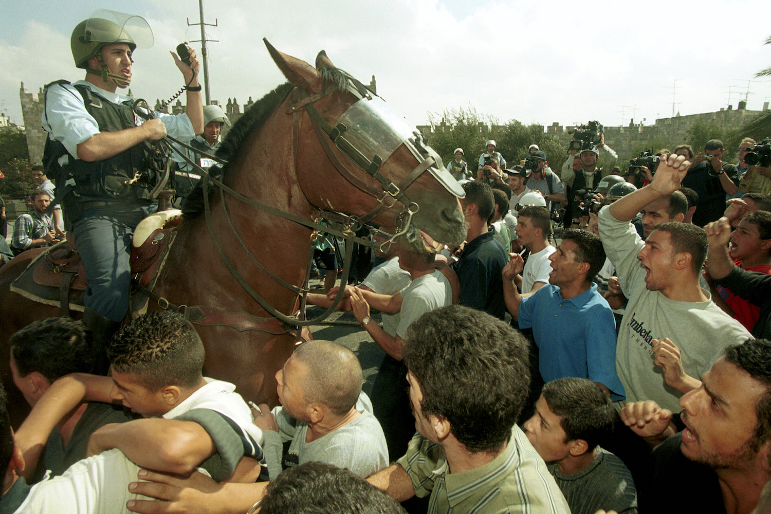 An Israeli police on horseback enters a crowd of Palestinians during clashes in the first days of the Second Intifada, October 20, 2000. (Flash90)