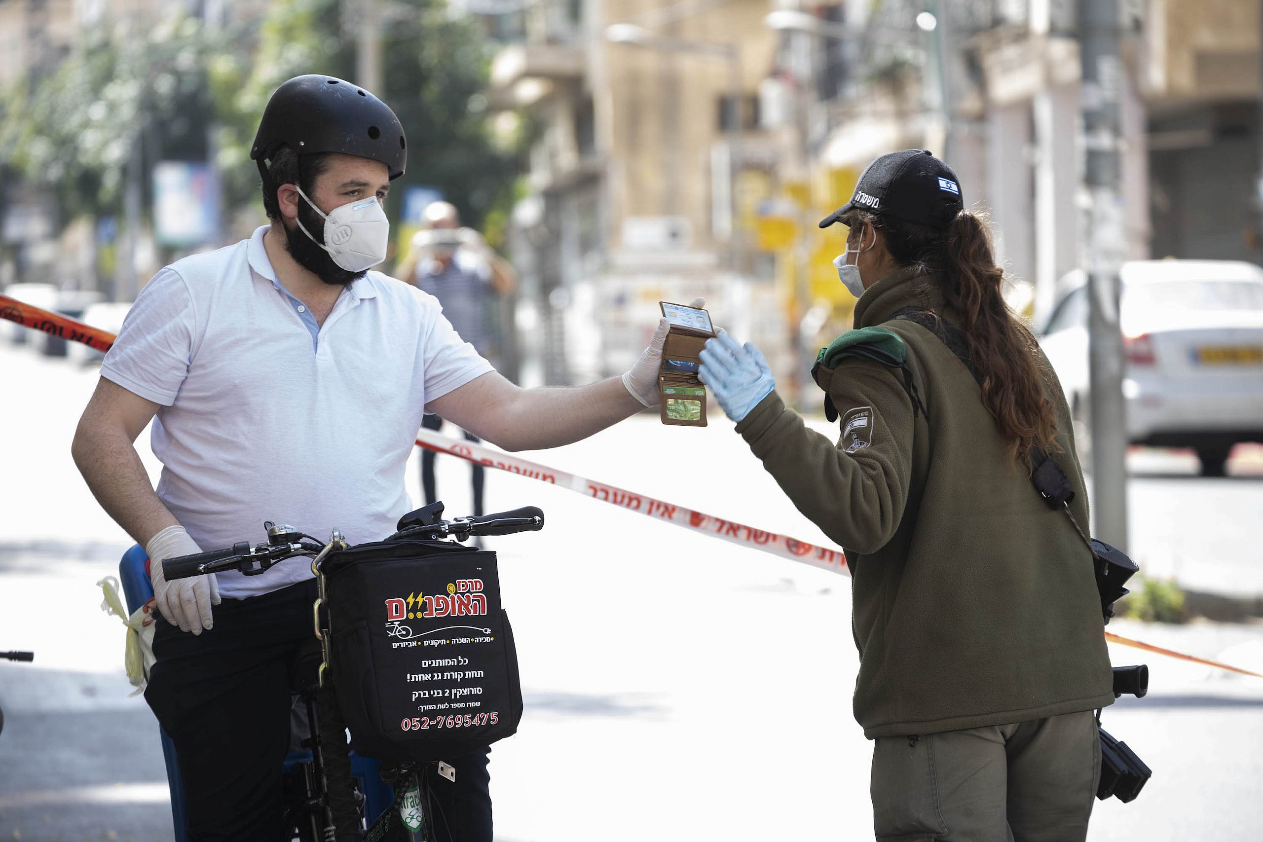 A Haredi man and an Israeli officer in Bnei Brak, during a city-wide closure due to the coronavirus, April 3, 2020. (Oren Ziv)