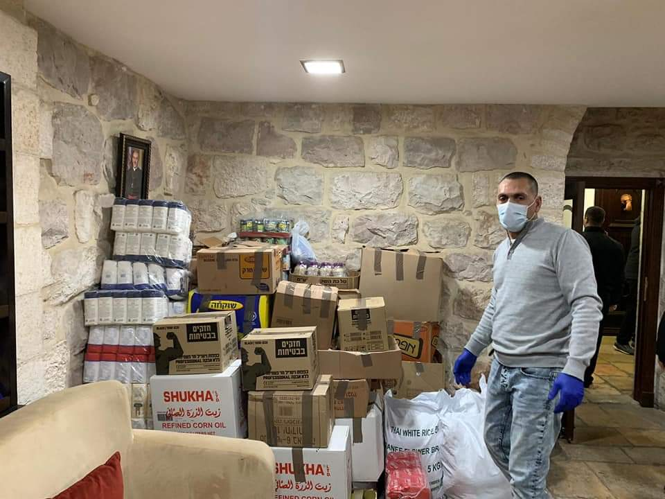 A volunteer in Haifa prepares food boxes for the elderly and families in need. (Courtesy of Bilal Alhousari)