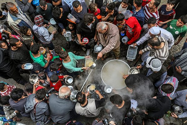 Residents of the Shuja'iyya neighborhood in Gaza huddle around Walid Hattab's cauldron of soup for iftar, April 25, 2020. (Mohammed Zaanoun)