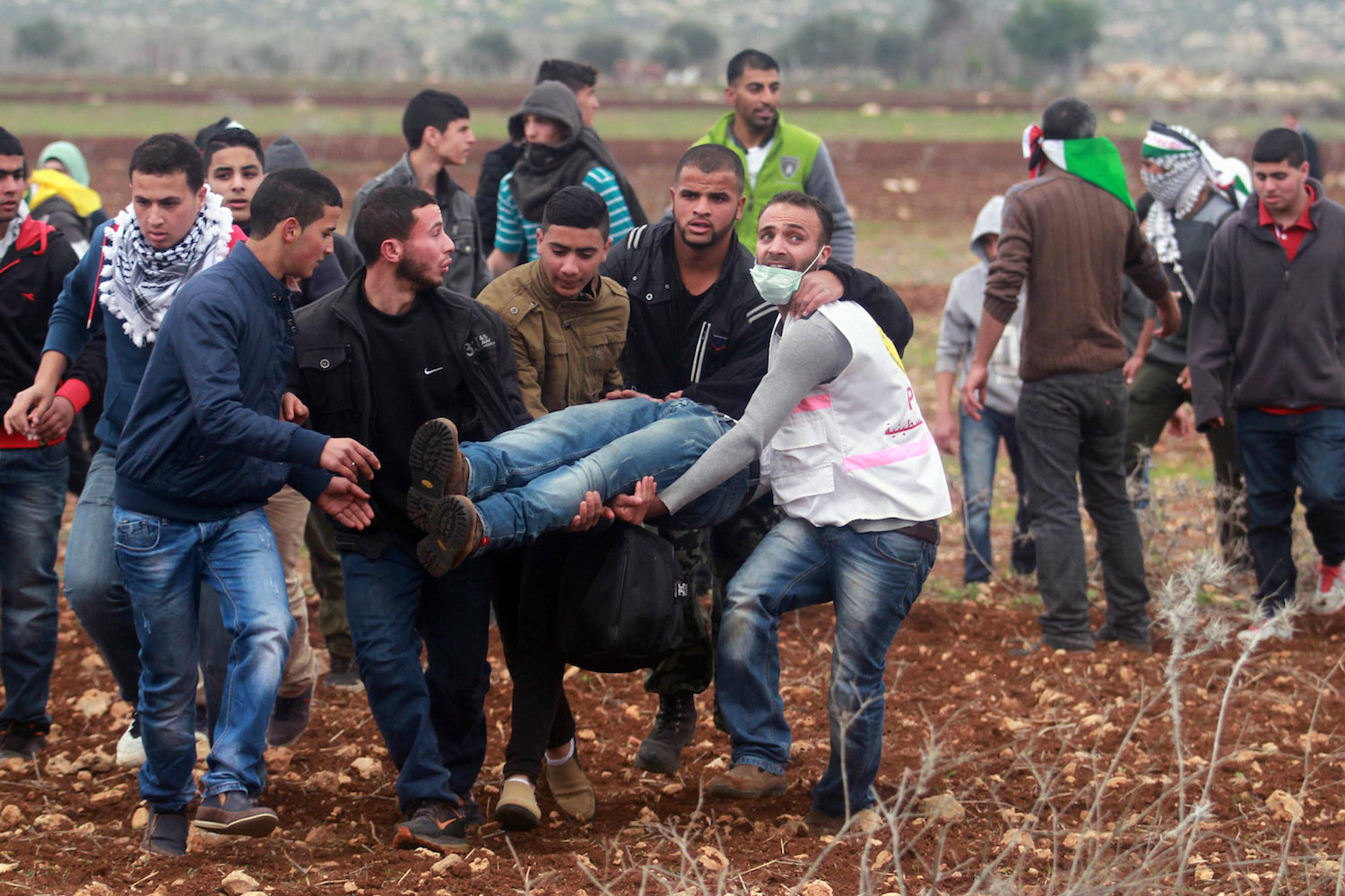 Palestinians carry a man wounded in clashes with Israeli forces following a demonstration against Israeli settlements in the West Bank village of Turmus Ayya, north of Ramallah, December 19, 2014. (Flash90)