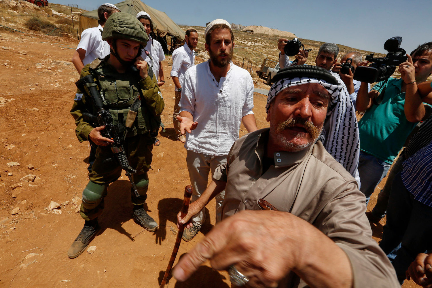 An Israeli settler argues with Palestinians during a protest against a new settler tent near the Pnei Hever settlement in the West bank village of Bani Naim on June 23, 2018. (Wisam Hashlamoun/Flash90)