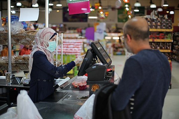 Palestinian workers wear face masks for fear of the coronavirus at a shop in Gaza City, March 9, 2020. (Ali Ahmed/Flash90)