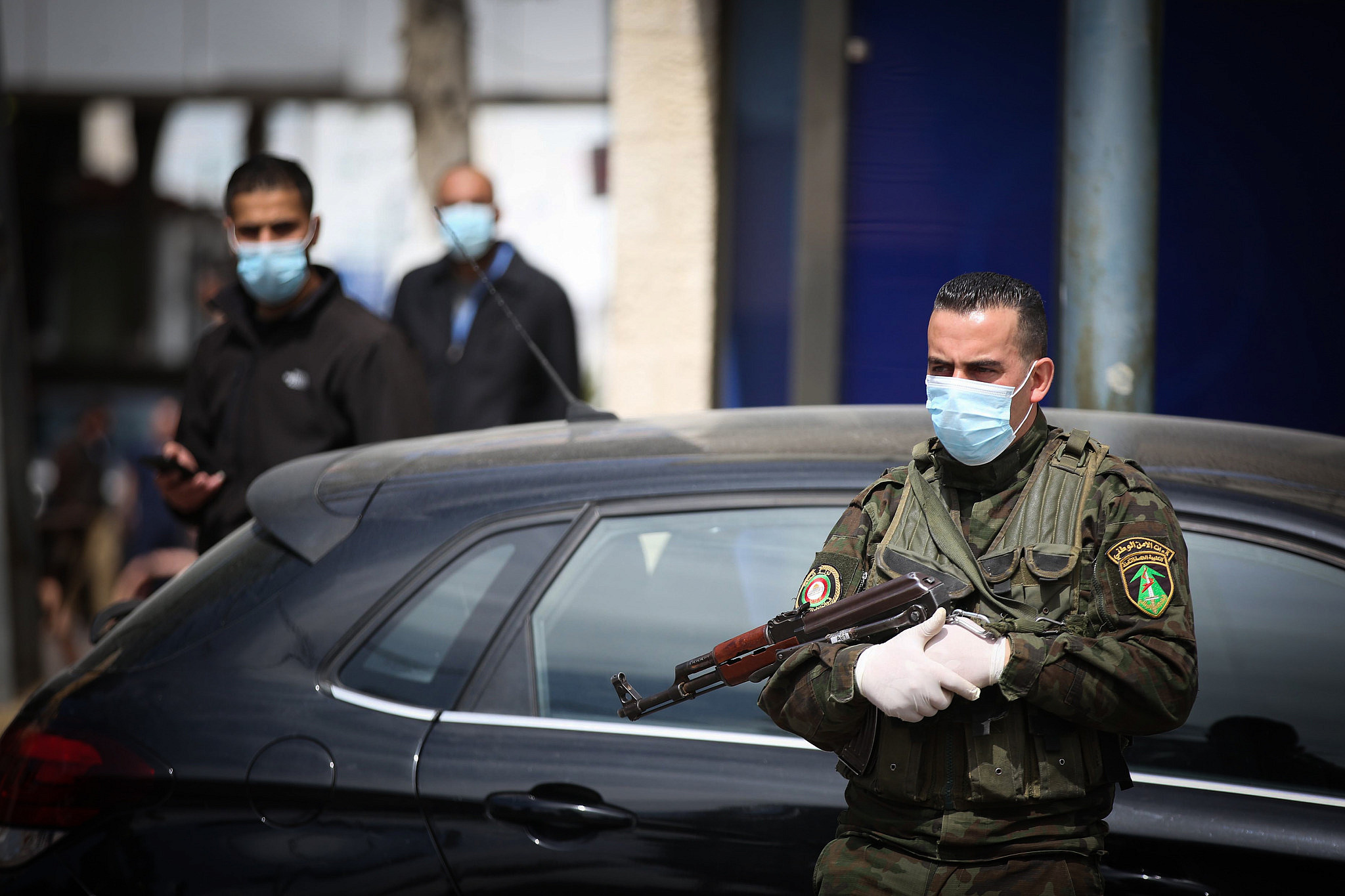 Palestinian municipal workers disinfect the parking lot of a hospital, in the West Bank city of Ramallah, March 12, 2020. (Flash90)