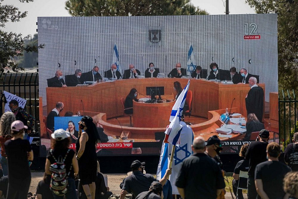 Israelis watch a Supreme Court session on petitions filed against the proposed government, outside the Knesset, Jerusalem, April 3, 2020. (Yonatan Sindel/Flash90)