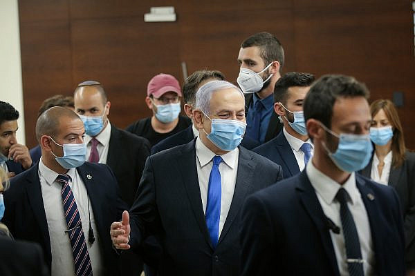 Israeli prime minister Benjamin Netanyahu walks in the Israeli parliament after presenting the 35th government of Israel to the Knesset, May 17, 2020. (Alex Kolomoisky/Pool)