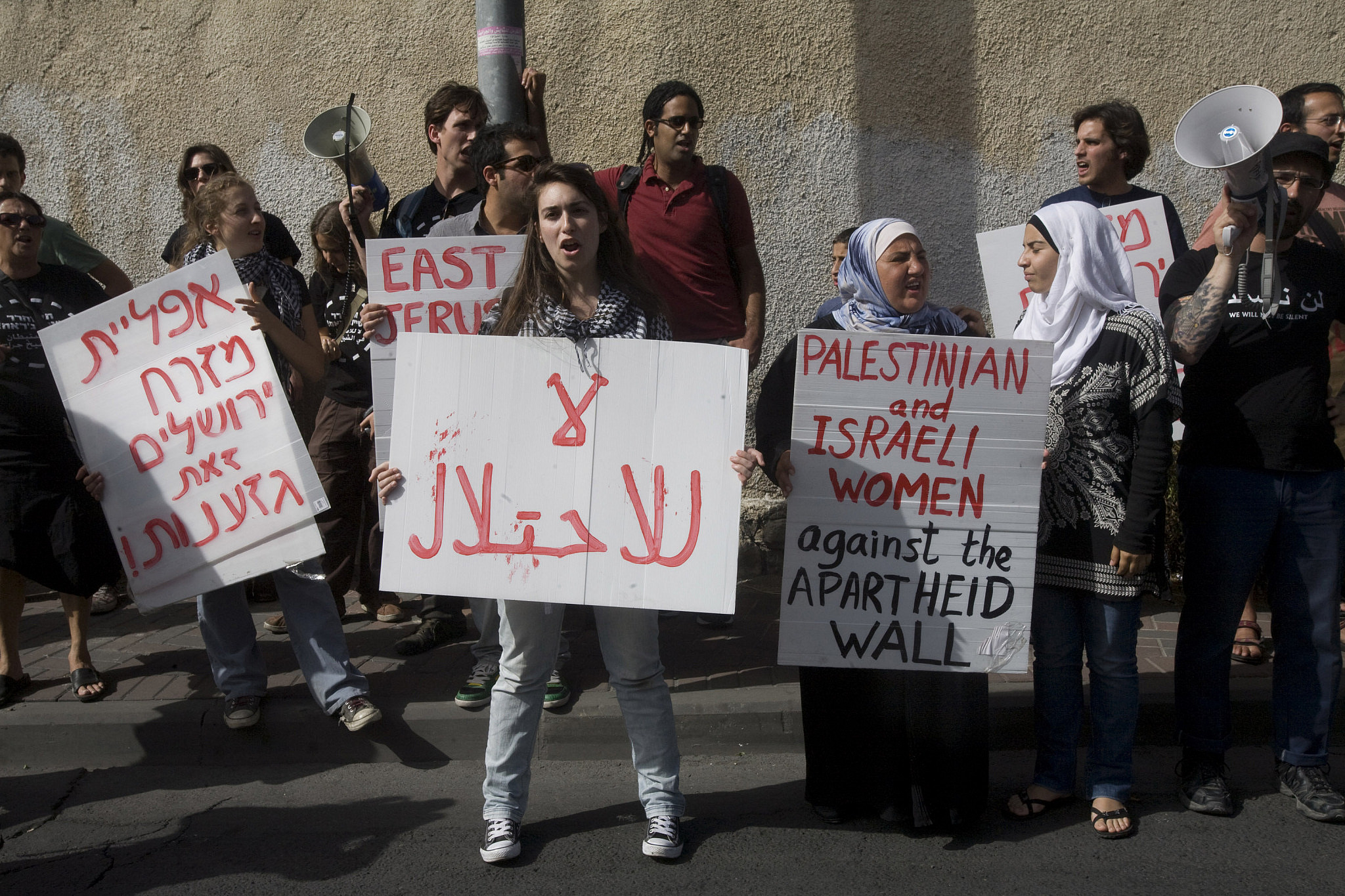 Israeli and Palestinian protesters hold signs during a demonstration against evictions and settlements in Sheikh Jarrah, East Jerusalem, May 14, 2010. (Oren Ziv/Activestills.org)