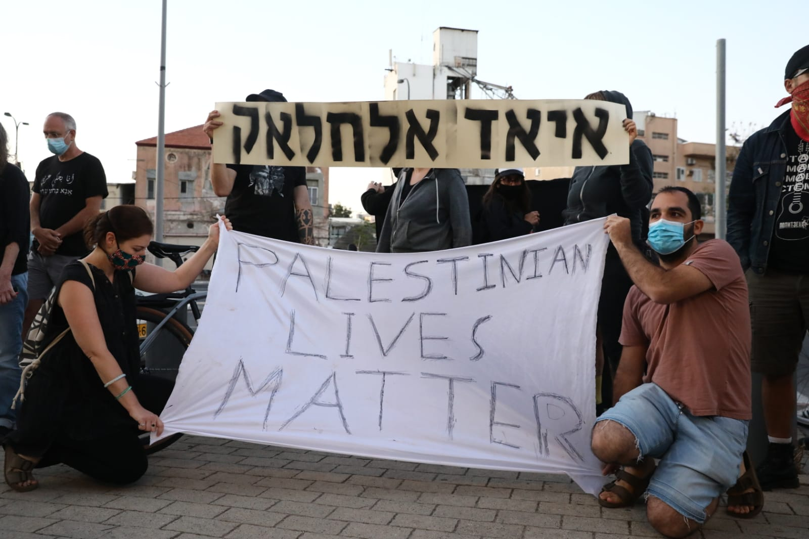 Israeli protesters demonstrate outside the Tel Aviv police headquarters against the killing of Iyad Hallak as well as increased police brutality against African asylum seekers in south Tel Aviv, May 30, 2020. (Oren Ziv)
