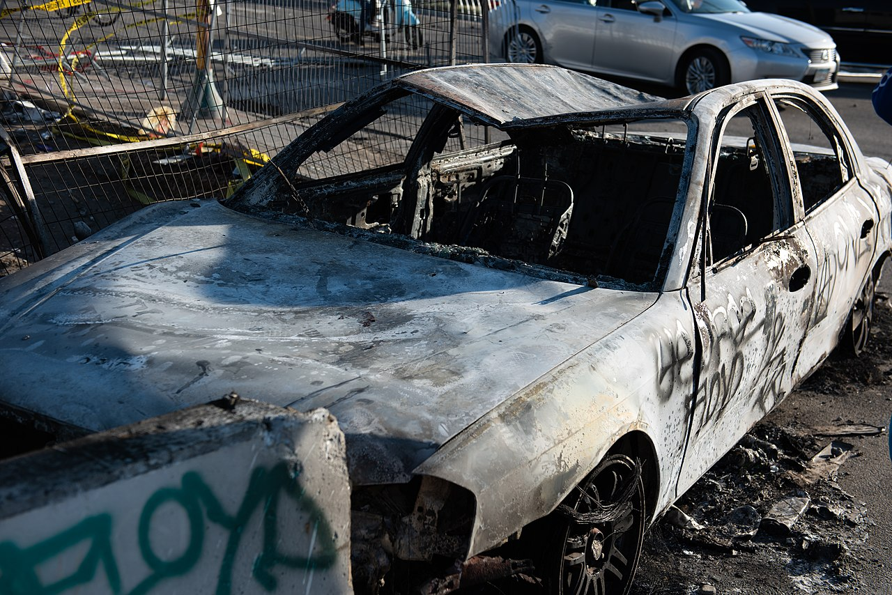 A destroyed car with graffiti in Minneapolis during demonstrations against the police killing of George Floyd. May 28, 2020. (Hungryogrephotos/Wikimedia Commons)