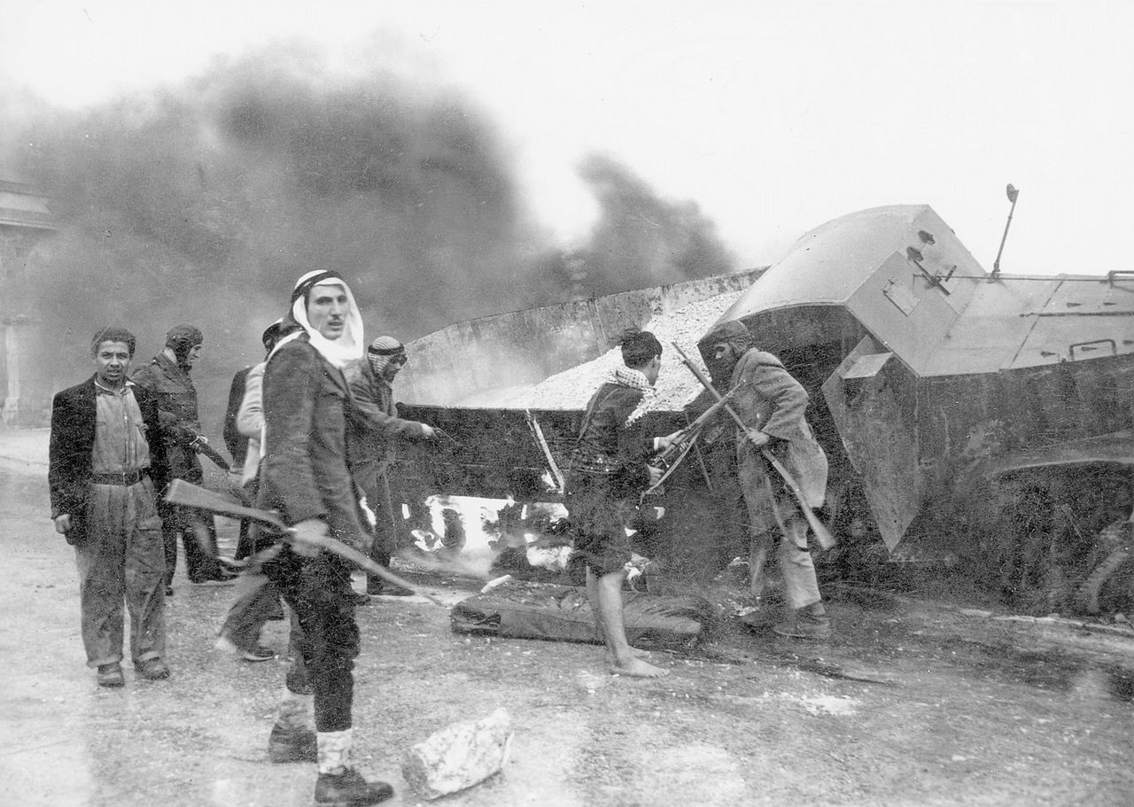 Palestinian Arab militia members, next to a burnt truck on their way to Jerusalem, circa 1948. (Palmach Photo Gallery/Wikimedia Commons)