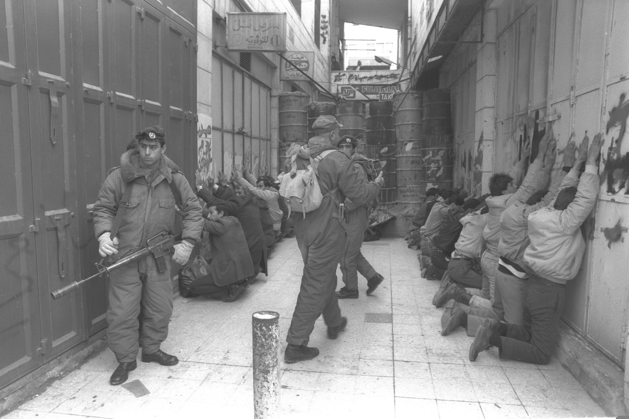 Border Police officers search Palestinians in Hebron, occupied West Bank, January 23, 1990. (Nathan Alpart/GPO)