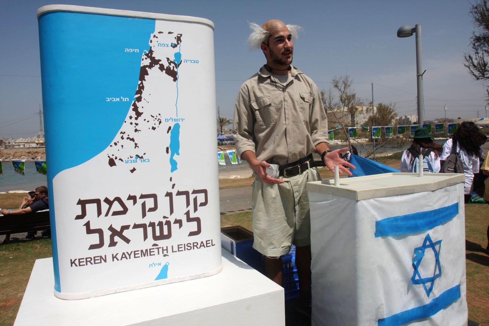 An Israeli dressed as David Ben-Gurion standing next to a KKL-JNF sign during celebrations of Israel's 61st Independence Day, in Tel Aviv. April 28, 2009. (Roni Schutzer/Flash90)