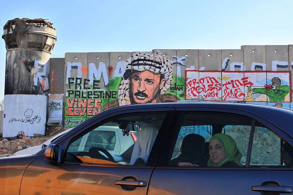 Palestinians in a car pass the separation wall at the Qalandiya checkpoint between the West Bank city of Ramallah and Jerusalem, on Aug 18, 2009. (Kobi Gideon/Flash90)