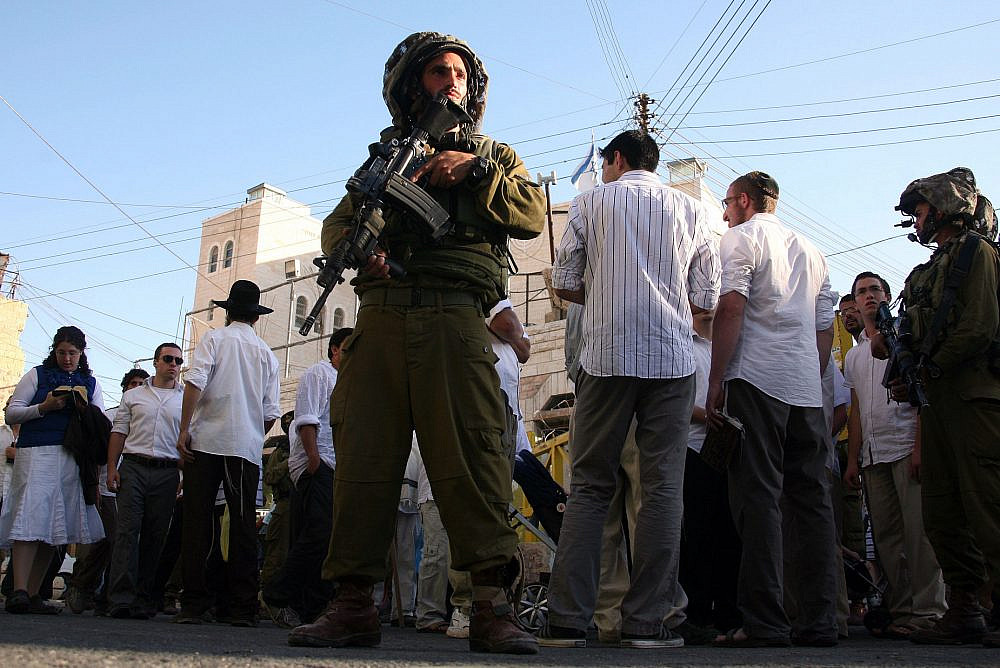 Israeli soldiers guard Jewish settlers as they walk around the Palestinian market in the old town of Hebron in the West Bank on September 4, 2010. (Najeh Hashlamoun /Flash90)