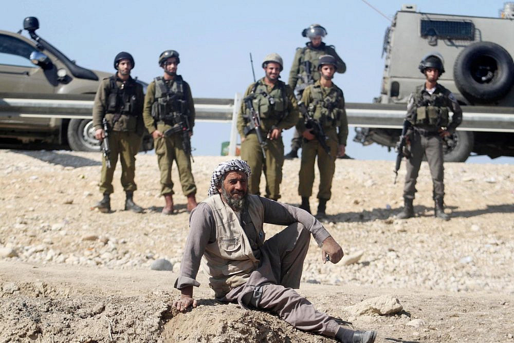 A Palestinian man rests by Israeli soldiers near the site of the old village known as Ein Hijleh, in the Jordan Valley near the West Bank city of Jericho, February 5, 2014. (Issam RiImawi/Flash90)