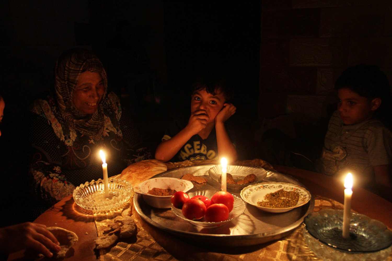 A Palestinian family eats dinner by candlelight during a power cut in the southern Gaza Strip, on July 29, 2015. (Abed Rahim Khatib/Flash90)