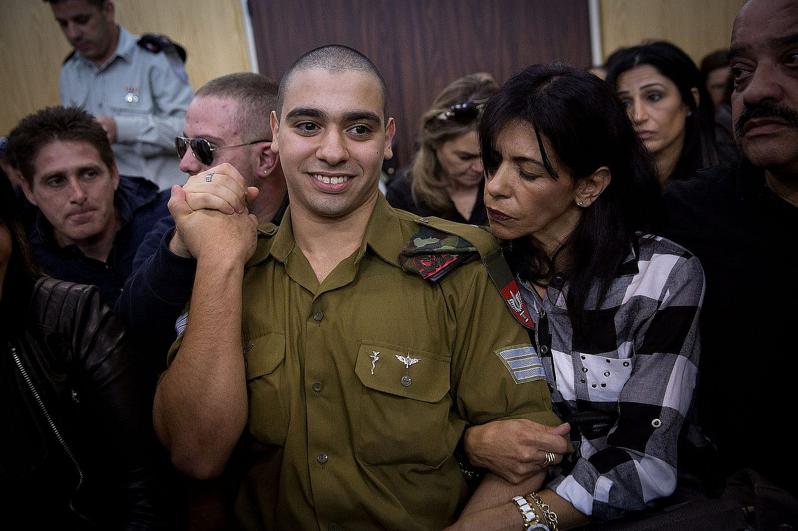 IDF Sgt. Elor Azaria, the Israeli soldier, who shot dead a disarmed and injured Palestinian attacker in Hebron a few months ago, with family and friends in a courtroom at the Kirya military base in Tel Aviv, on January 4, 2017. (Miriam Alster/Flash90)