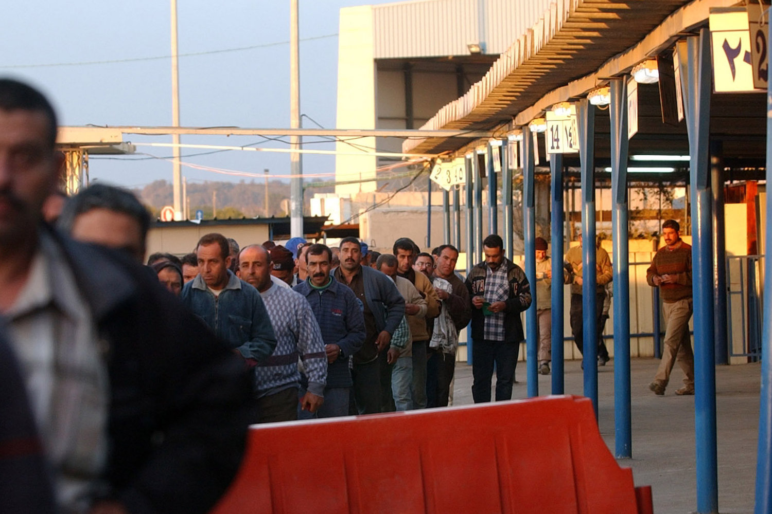 Palestinian workers return to the Gaza Strip at the end of their work day from the Erez Industrial Zone. Erez Crossing, Gaza, March 9, 2004. (Sharon Perry/Flash90)