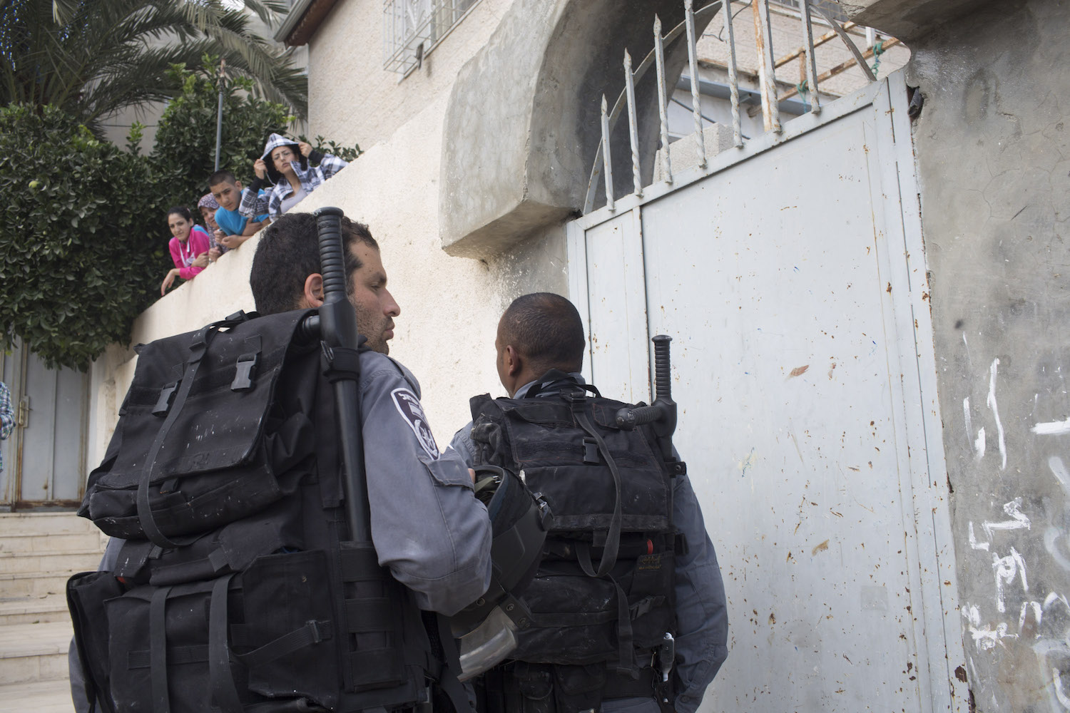 Israeli police officers enter the house of the Hayat family in Silwan neighbourhood in East Jerusalem, after Israeli settlers took over one apartment in the building, September 30, 2014. (Oren Ziv/Activestills.org)