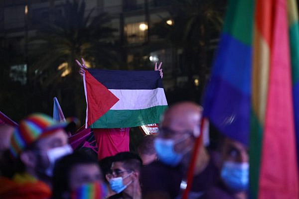 A left-wing holds up a Palestinian flag at Tel Aviv Pride, June 28, 2020. (Oren Ziv/Activestills)
