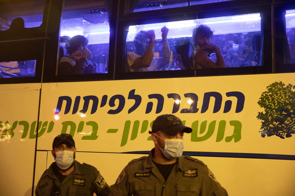 Protesters arrested during clashes with police in central Jerusalem are seen on a bus belonging to a settlement organization. Clashes erupted after a mass protest outside the Prime Minister's Residence, demanding Benjamin Netanyahu step down, July 14, 2020. (Oren Ziv)
