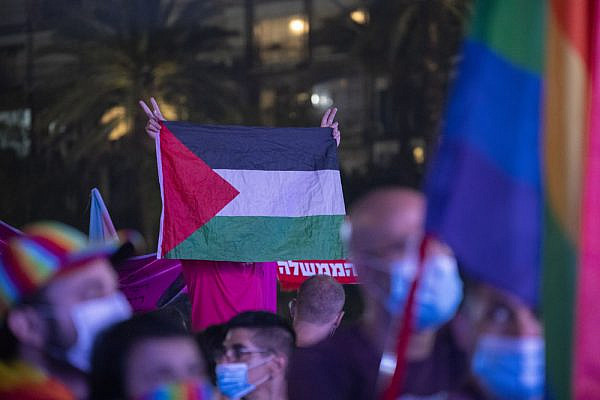 A left-wing activist holds up a Palestinian flag at Tel Aviv Pride, June 28, 2020. (Oren Ziv/Activestills)