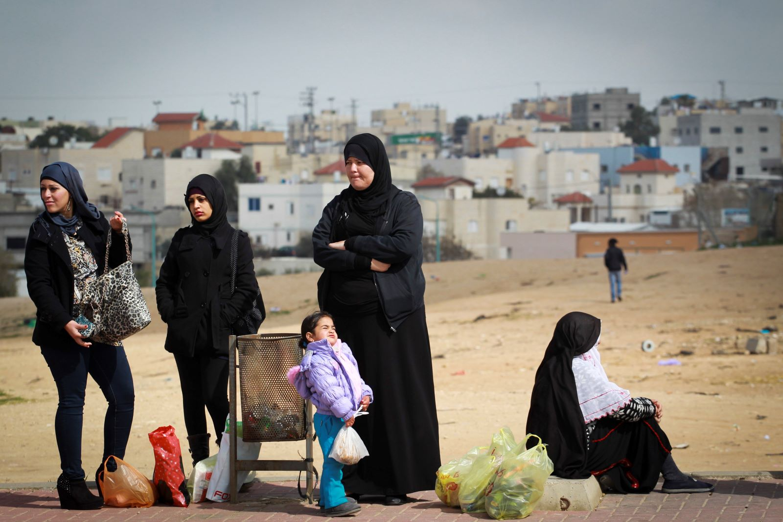 Bedouin women wait for a bus in the Bedouin city of Rahat in southern Israel, February 16, 2014. (Hadas Parush/Flash90)
