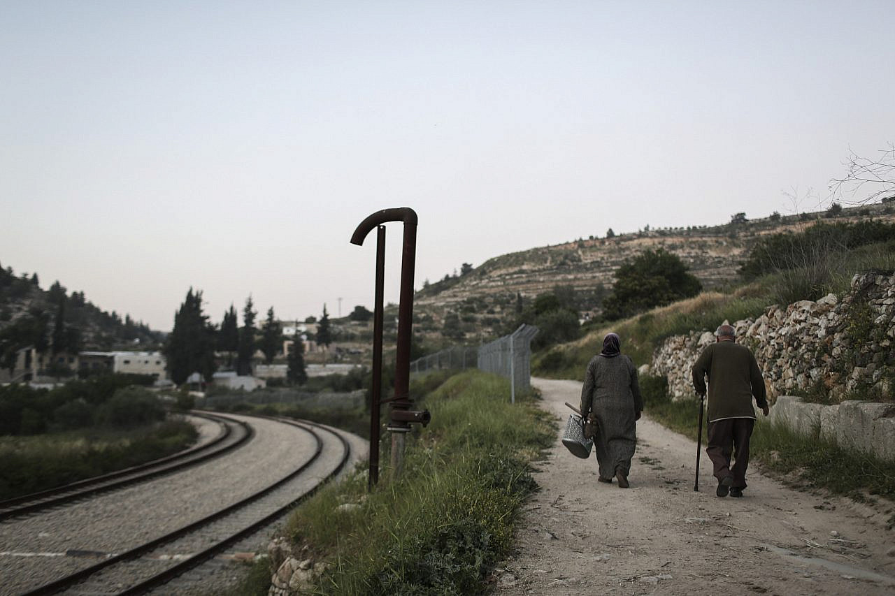 A Palestinian couple seen walking home along the railway tracks after a day of farming work, in the Palestinian village of Battir, West Bank, April 23, 2014. (Hadas Parush/Flash90)
