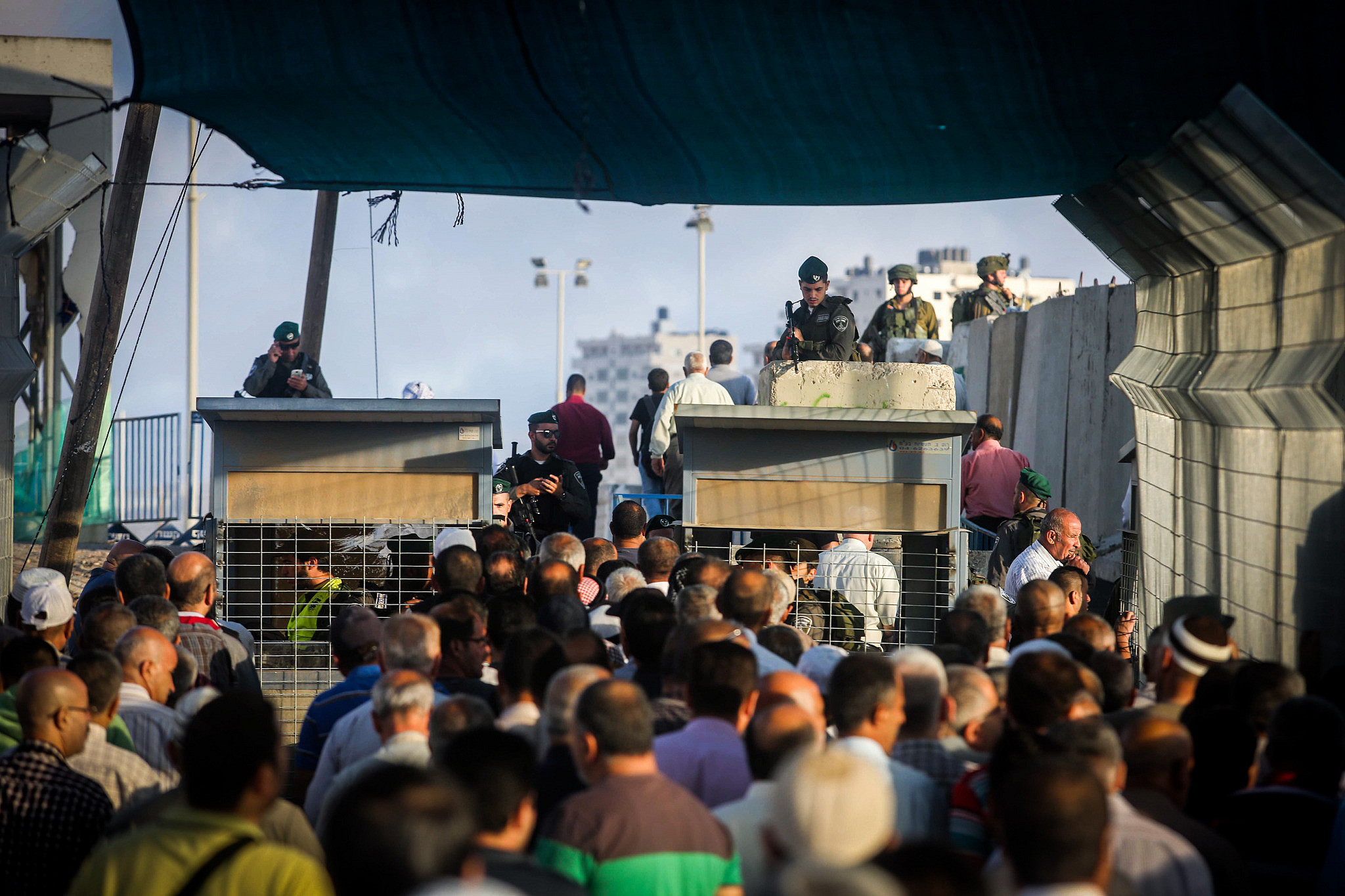 Palestinians cross the Qalandiya checkpoint, outside of the West bank city of Ramallah, as they head to the Al-Aqsa mosque compound in Jerusalem's Old City to attend the first Friday prayers of Ramadan. June 10, 2016. (Flash90)