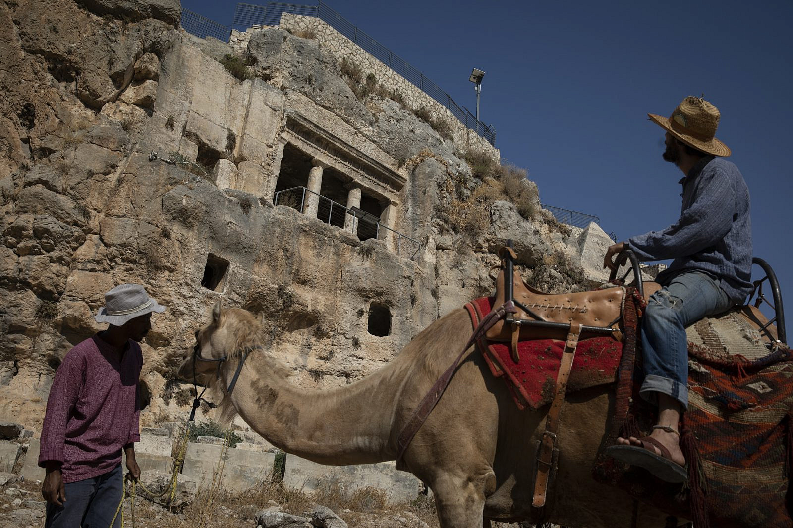 An Israeli man rides a camel for tourists to walk through the Tomb of Zechariah and the Tomb of Benei Hezir. August 4, 2019. (Hadas Parush/Flash90)
