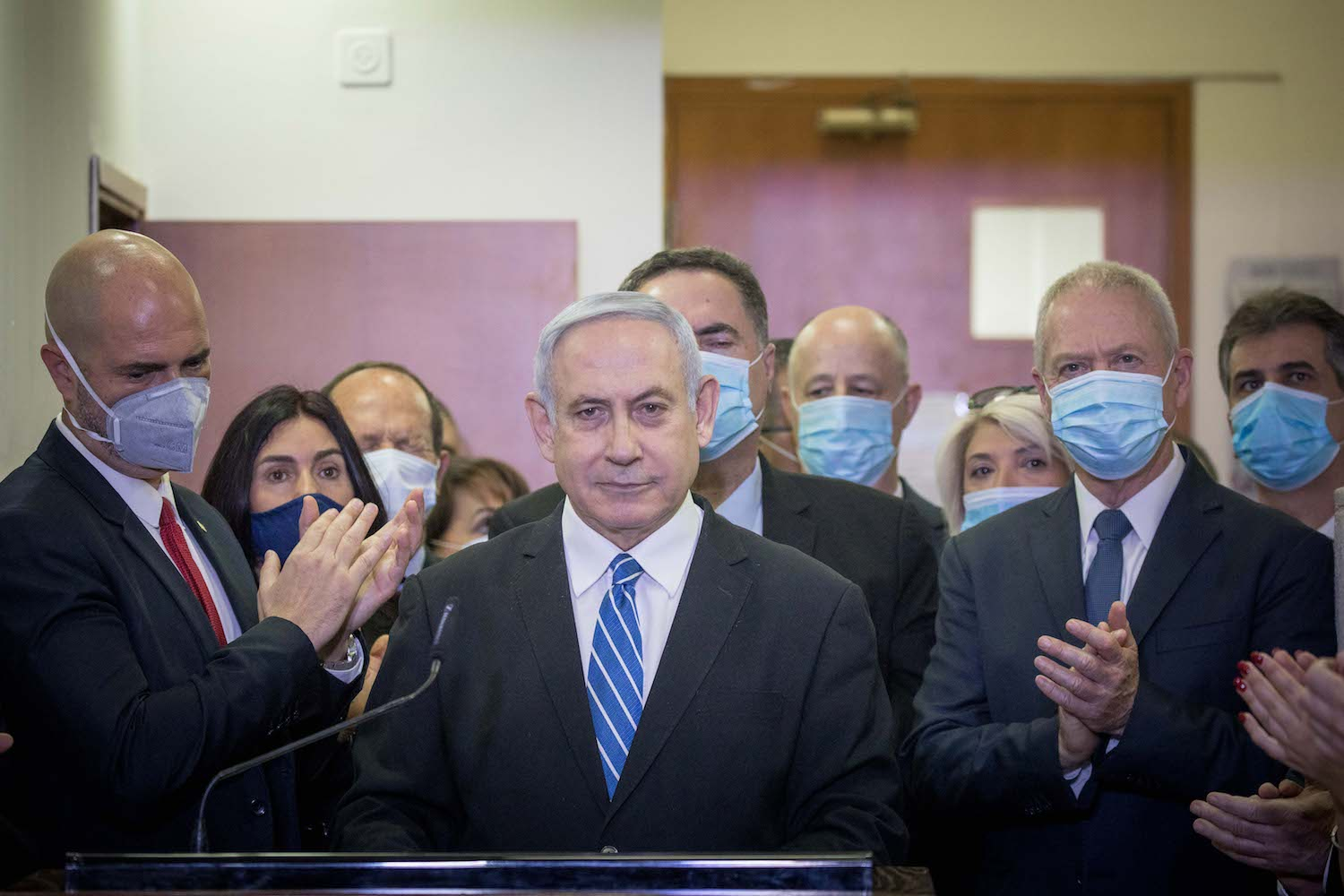 Israeli Prime Minister Benjamin Netanyahu is surrounded by Likud lawmakers as he gives a press statement ahead of the start of his trial at the District Court in Jerusalem, May 24, 2020. (Yonatan Sindel/Flash90)