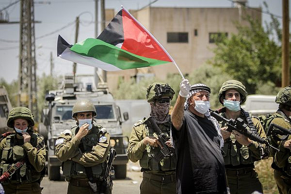 Israeli security forces next to Palestinians protesting Israel's plan to annex parts of the West Bank, Haris, June 26, 2020. (Nasser Ishtayeh/Flash90)