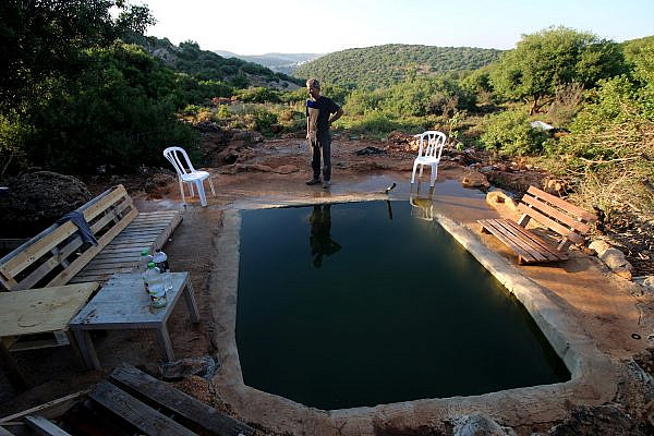Amer Abu Hijleh near the pool that settlers built on his land in the occupied West Bank. (Ahmad Al-Bazz/Activestills)