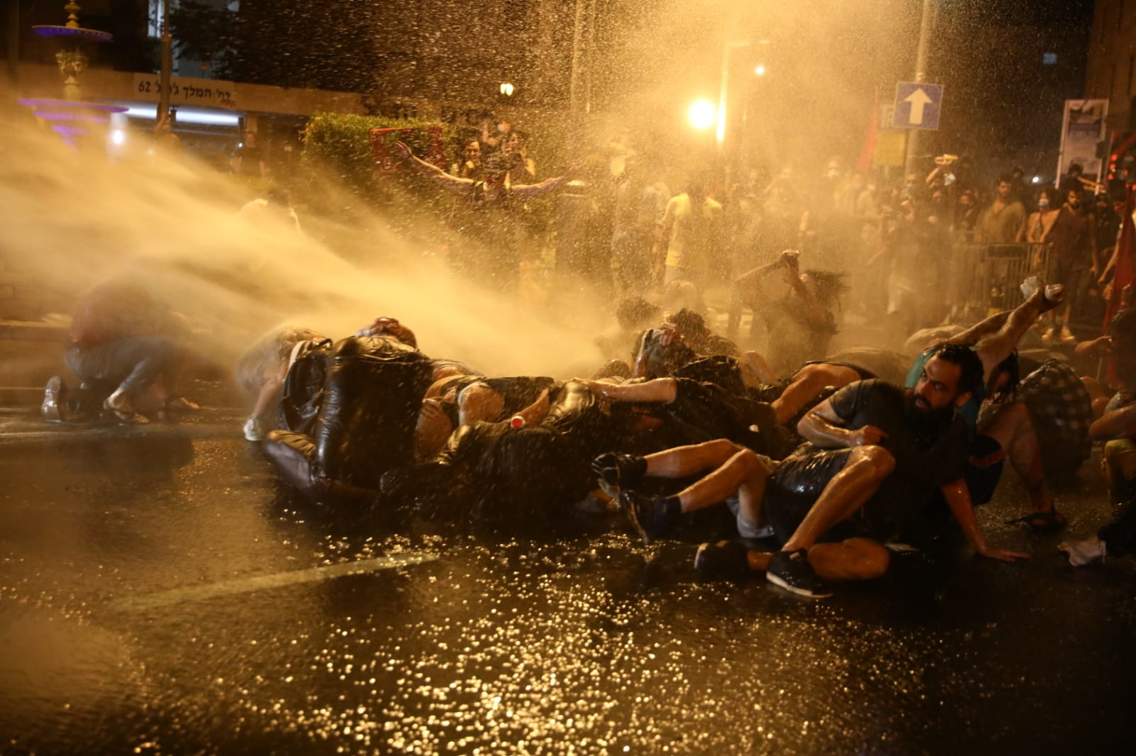 A police water cannon douses protesters in central Jerusalem during clashes that followed a mass demonstration outside the Prime Minister's Residence, July 14, 2020. (Oren Ziv/Activestills)