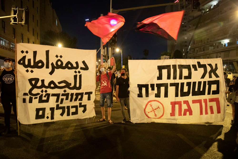 Israeli protesters carry signs saying 'Democracy for all' and 'Police violence kills' during anti-Netanyahu demonstrations in Jerusalem, July 2020. (Oren Ziv/Activestills)