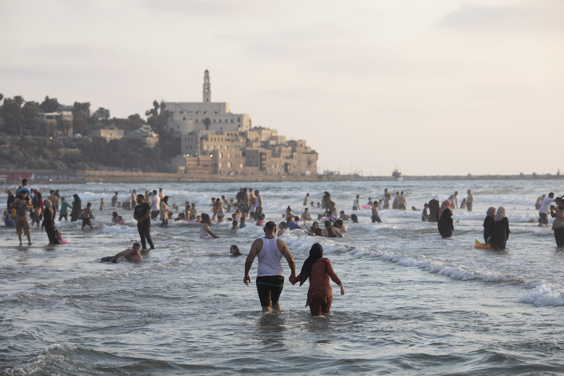 Palestinian families, some of whom are from the West Bank, enjoy the sea in Jaffa. (Activestills)