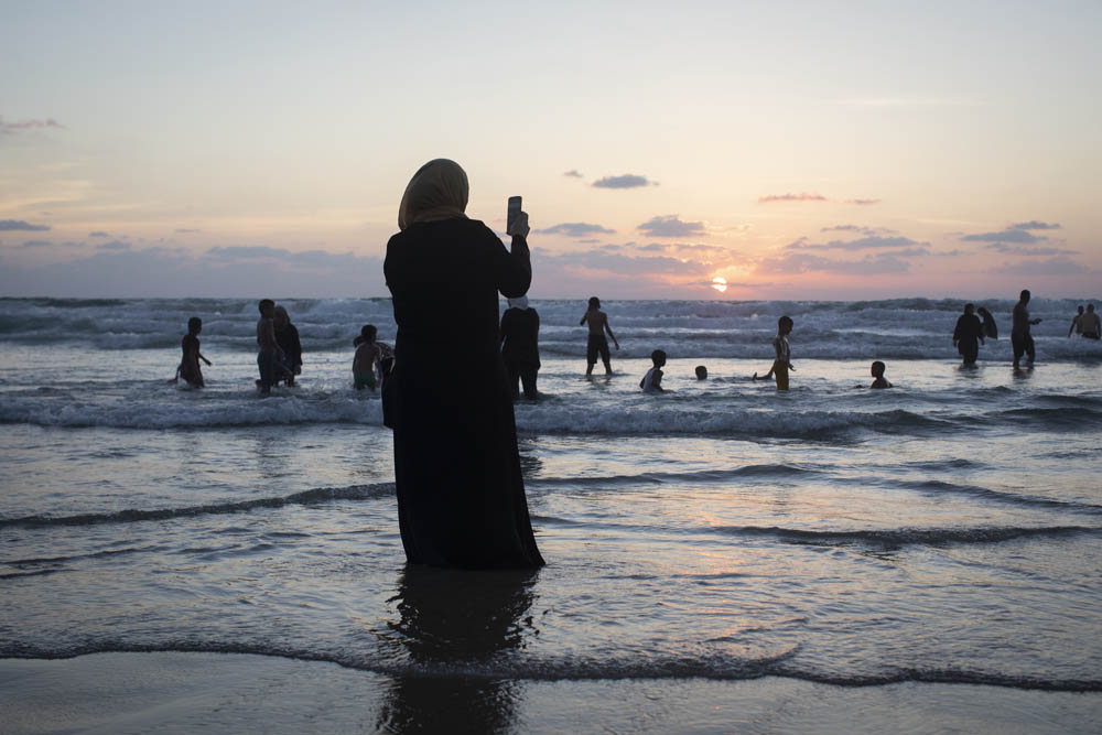 A Palestinian woman takes a photo of the sunset in Jaffa. (Activestills)