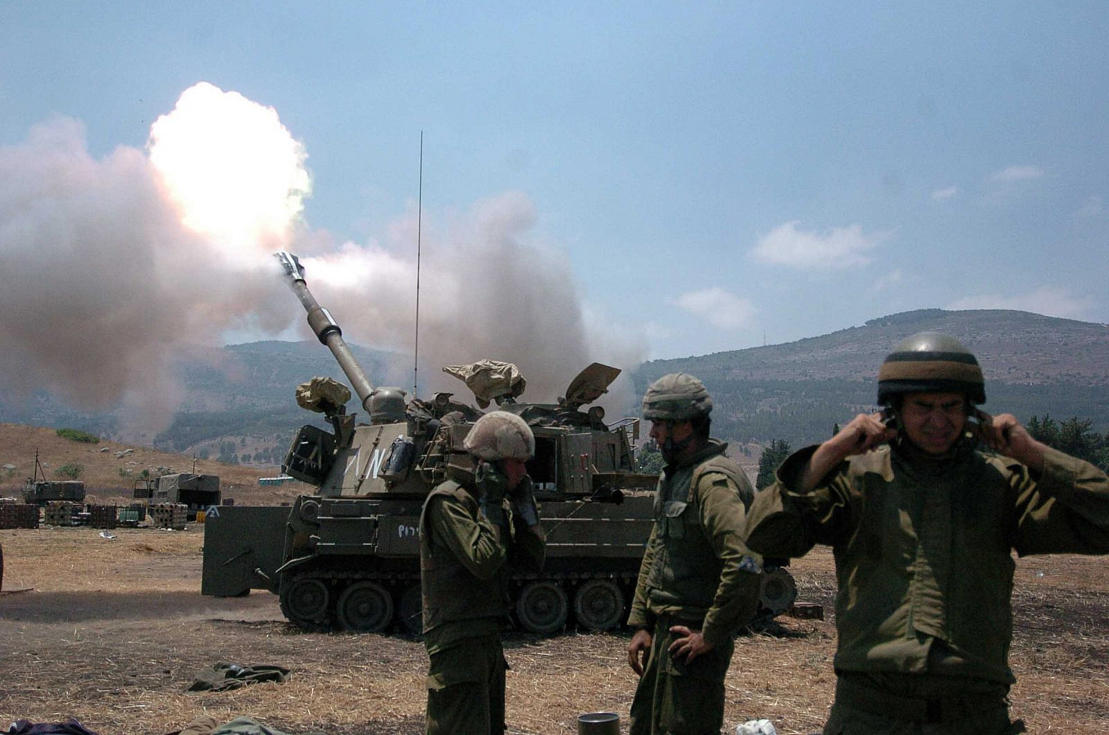 Israeli soldiers cover their ears as a tank fires into Lebanon from Kiryat Shmona on July 20, 2006. (Guy Assayag/Flash90)