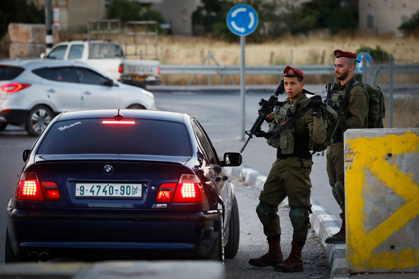 Israeli soldiers check IDs of Palestinian drivers at a checkpoint at the entrance of the West Bank city of Hebron, July 2, 2019. (Wisam Hashlamoun/Flash90)