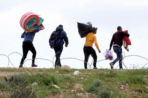 Palestinian workers from Hebron carry personal belongings as they cross through a hole in the Israeli security fence, after entrance into Israel was banned following the spread of the coronavirus, near the West Bank city of Hebron, March 22, 2020. (Wisam Hashlamoun/Flash90)